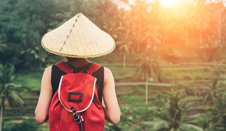 Young lady with traditional Asian hat and backpack standing and looking at tea plants (intentional sun glare)